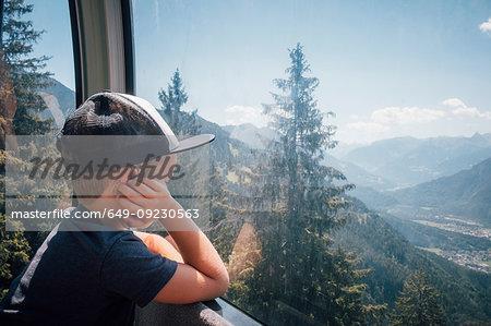Boy contemplating view of valley, Bludenz, Vorarlberg, Austria