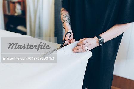 Fashion designer cutting paper pattern