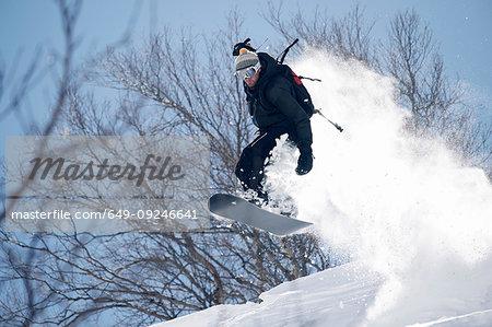 Male snowboarder snowboarding mid air on  mountainside, Alpe-d'Huez, Rhone-Alpes, France