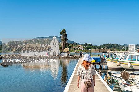 Tourist walking on bridge leading to Vlacherna Monastery, island on background, Corfu, Kerkira, Greece