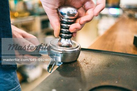 Barista tamping coffee in coffee bar