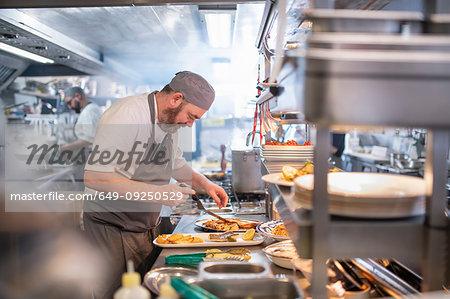 Chef preparing dishes in Italian restaurant kitchen