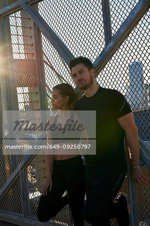 Friends taking break beside fenced wall in sports stadium