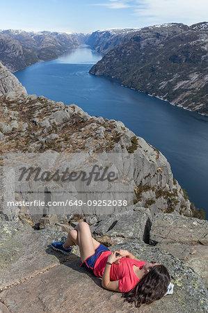 Hiker resting on cliff top, Preikestolen (Pulpit Rock), Lysefjord, Norway, Stavanger