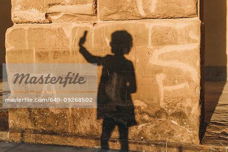 Shadow of woman taking selfie on stone wall