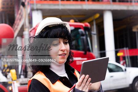 Female surveyor looking at digital tablet on construction site