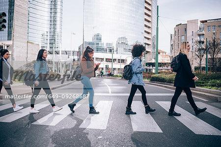 Friends crossing road on zebra crossing