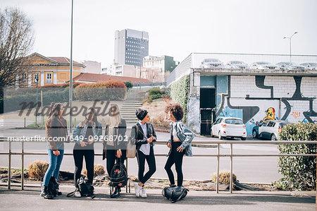 Friends talking in street, Milan, Italy