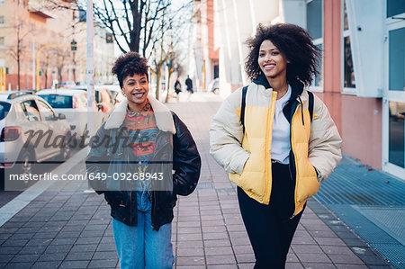 Two cool young women strolling on urban sidewalk