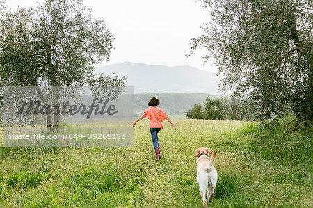 Girl running with labrador dog in scenic field landscape, rear view, Citta della Pieve, Umbria, Italy