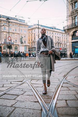 Stylish man walking over tram tracks in piazza, Milan, Italy