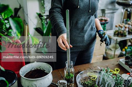 Woman filling glass bottle with plants in nursery