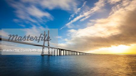 Vasco da Gama Bridge spanning Tagus river at sunset, Portugal