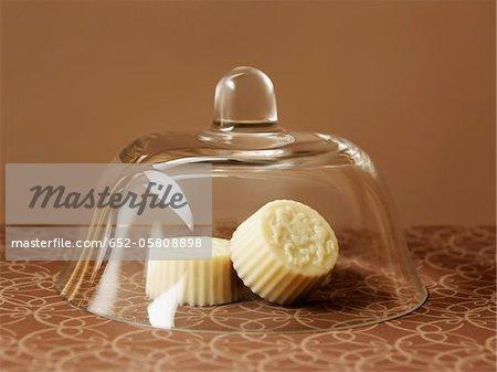 Three white chocolates under a glass dome