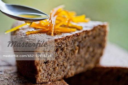 Coating a slice of hazelnut cake with orange juice