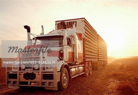 Semi-truck in remote landscape at sunset