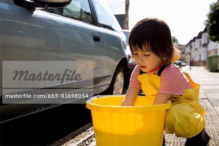 A young boy washing a car