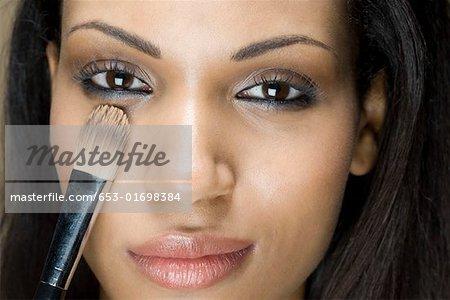 A woman applying eye shadow