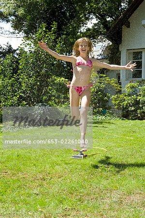 A girl running through a sprinkler