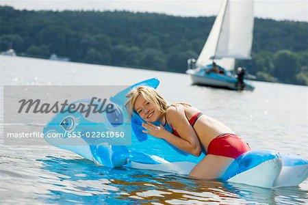A girl lying on an pool raft on a lake