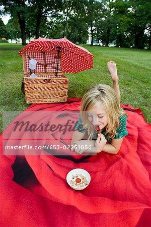 A girl with a bowl of yogurt, granola & strawberries at a picnic