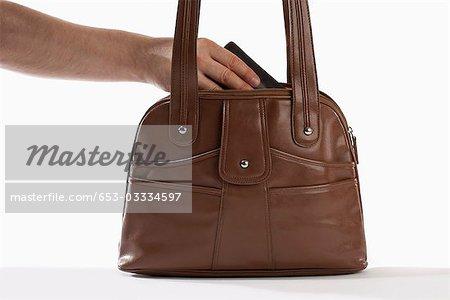 Detail of a man reaching into a handbag