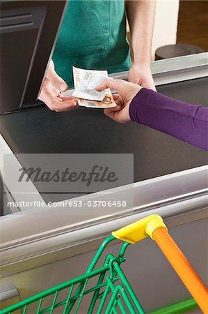 A customer handing a cashier cash at the supermarket