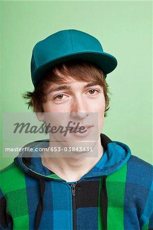 A teenage boy wearing a hoodie and baseball cap, portrait, studio shot