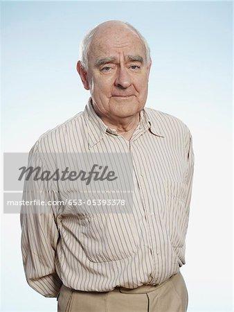 Profile of senior man with hands behind back looking at camera