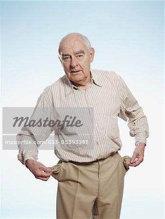 Senior man turns his pockets inside out to symbolize having no money