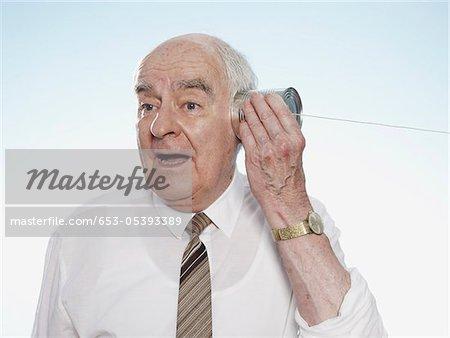 Senior man listening on tin can phone