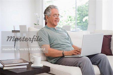 A senior man using a laptop at home