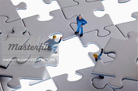 Miniature workmen working on assembling a jigsaw puzzle