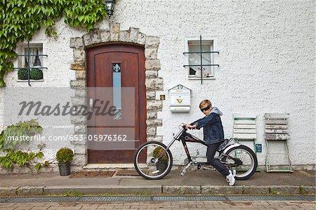 An adolescent boy posing on a vintage motorbike