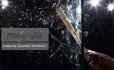 Detail of a man smashing glass with a baseball bat