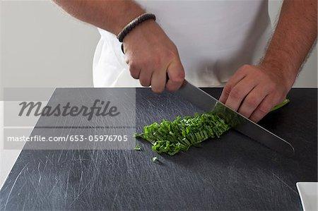 Detail of a man chopping fresh herbs
