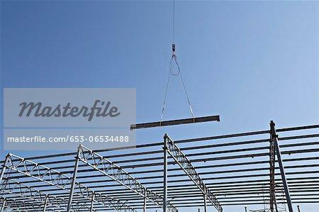 Crane lowering steel beam towards construction frame
