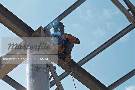 Welder high up on steel beam