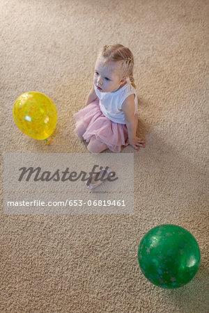 Little girl between two balloons as her ballet shoe lies on the floor