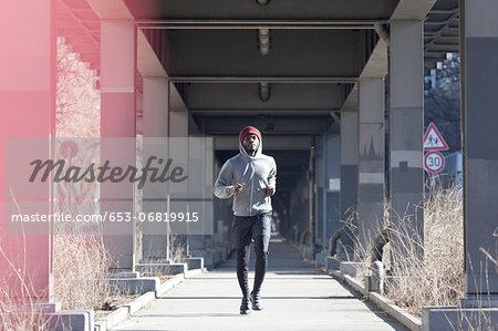 A hip young man jogging on a city sidewalk under a bridge