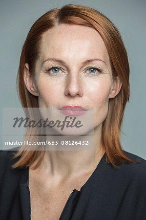 Portrait of confident mature woman against gray background