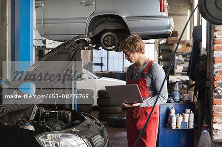 Mechanic using laptop while examining car engine at garage