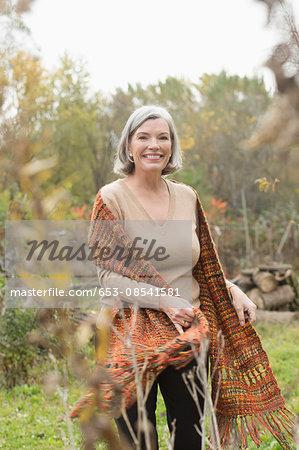 Portrait of happy mature woman at park during autumn