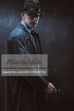Portrait of confident man holding gun standing against black wall