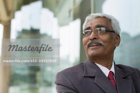 India, Smiling senior businessman outside office building
