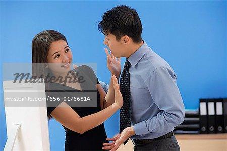 Woman pushing away businessman