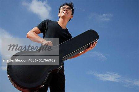 Man holding guitar case