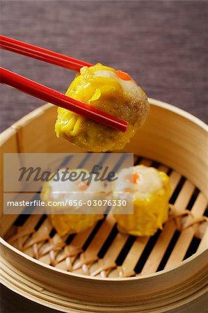 red chopsticks holding dim sum