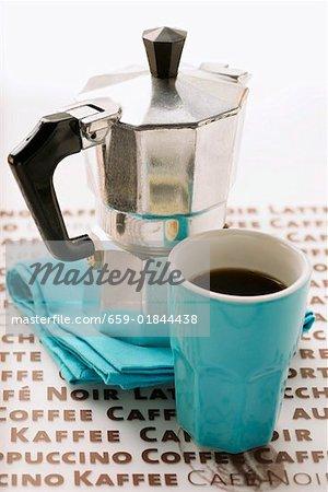 Blue espresso cup in front of espresso machine