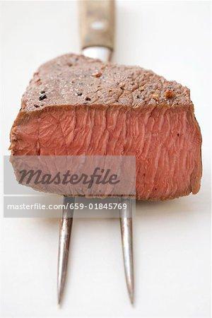 Beef steak, a piece cut off, on meat fork